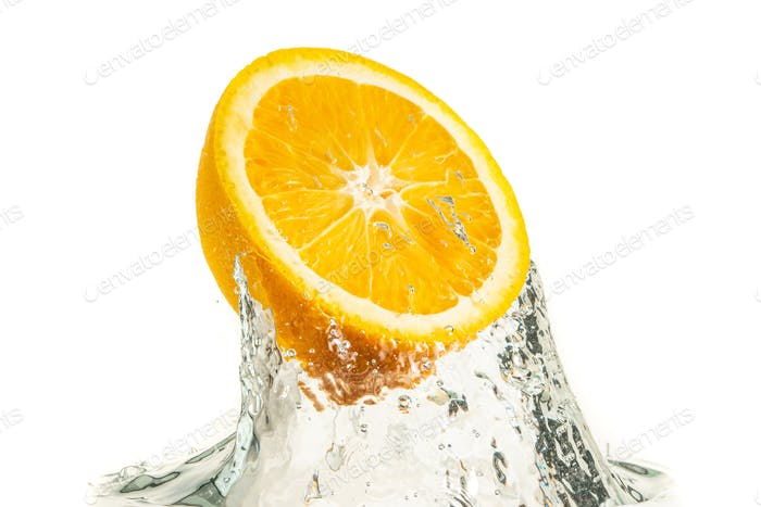 Orange half splashing into water and sinking isolated on white background. Citrus drink concept.