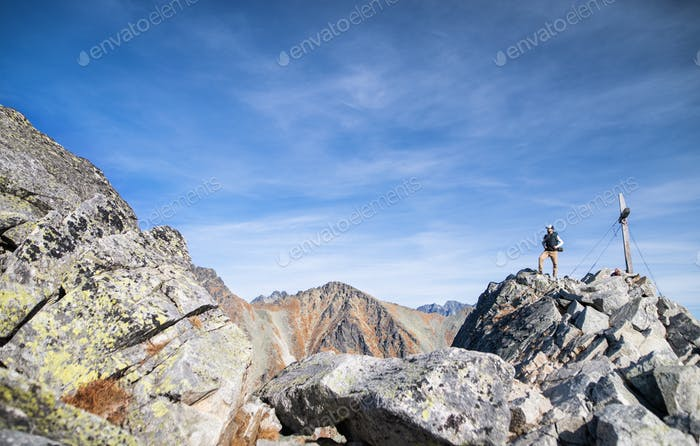 Mature man with backpack hiking in mountains in autumn