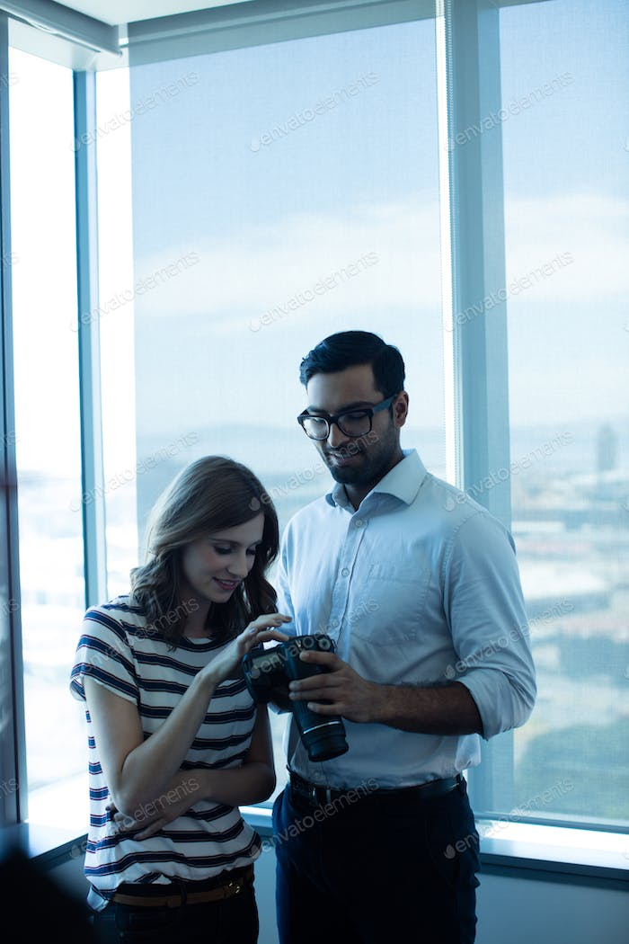 Smiling business couple holding digital camera against glass window