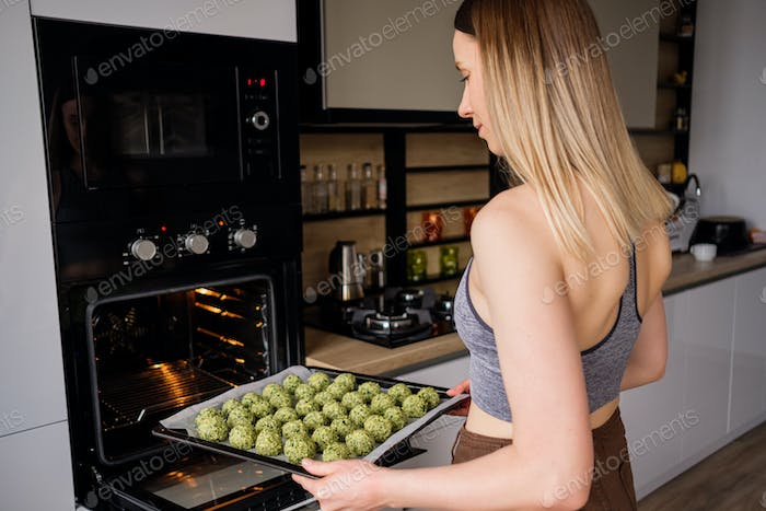 Lovely fit woman put in the oven a tray with falafel