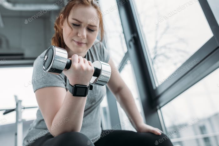 Curvy girl training biceps with dumbbell in gym