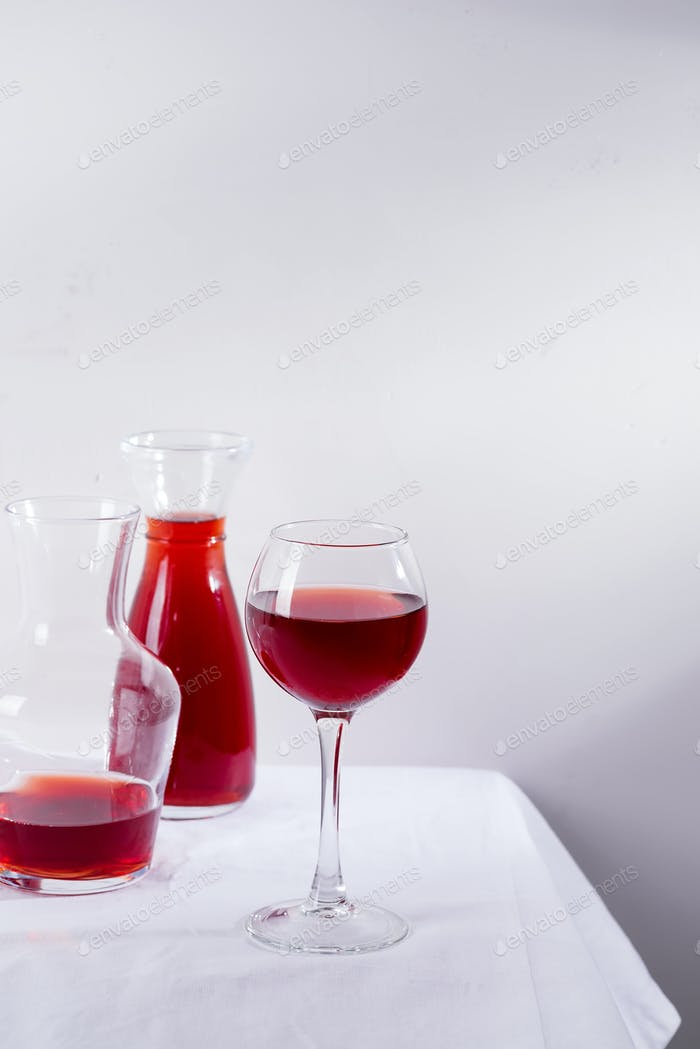 red wine in a wineglass, decanter and bottle with shadows isolated on white textile background