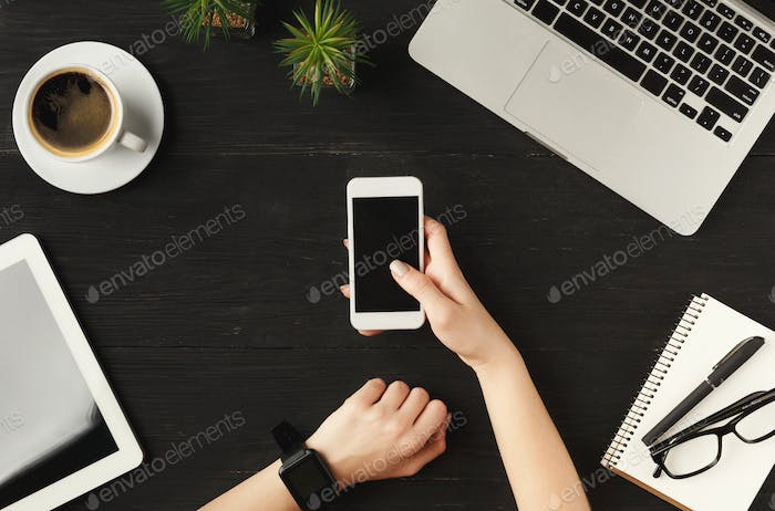 Woman's hands holding smartphone, top view