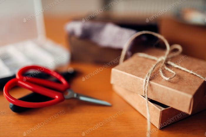 Needlework gift and scissors on wooden table