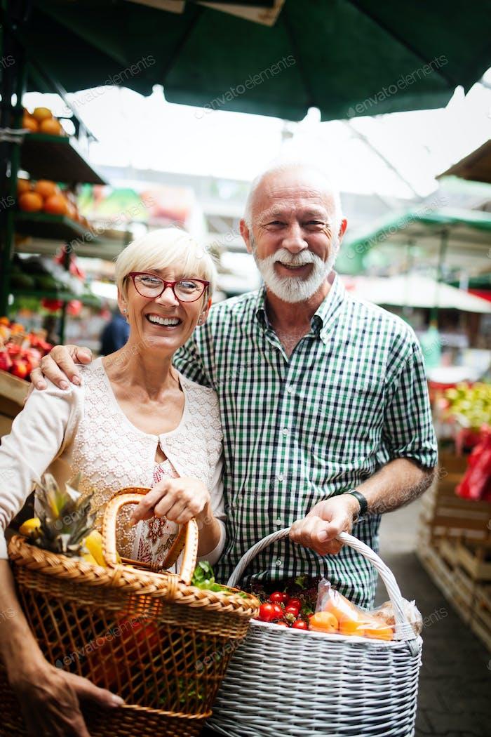 Портрет красивой пожилой пары на рынке buing еды