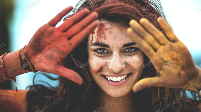 Young woman holding paint covered hands up to her face, one red and one yellow, smiling, Framing her