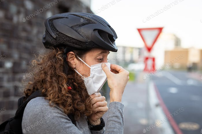 Caucasian woman putting on a protective mask and wearing a cycling helmet in the streets