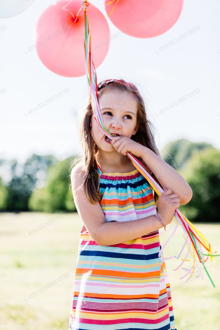Kleines Mädchen kauen Ballon Saiten in Ihr Mund