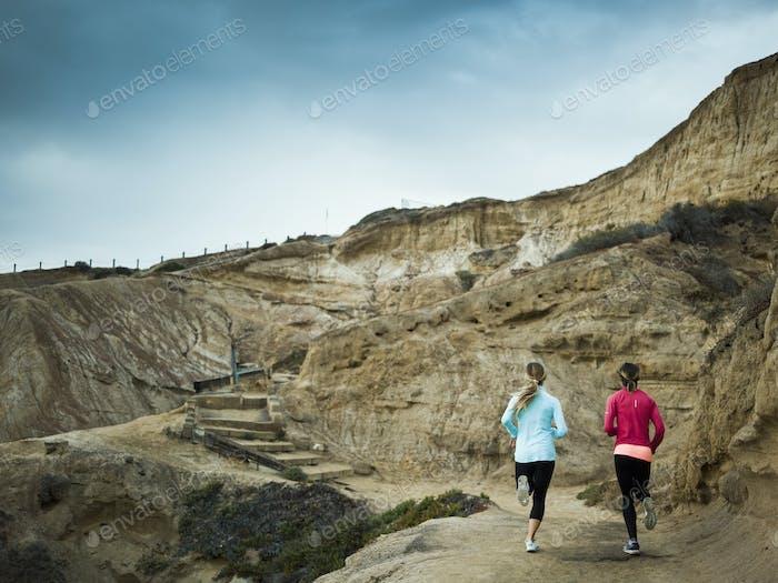 Two women jogging along a quarry trail.