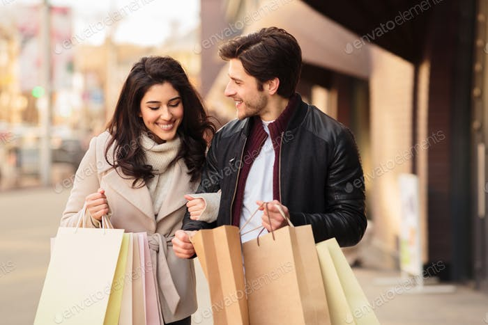 Young shopaholics looking into shopping bags outdoors