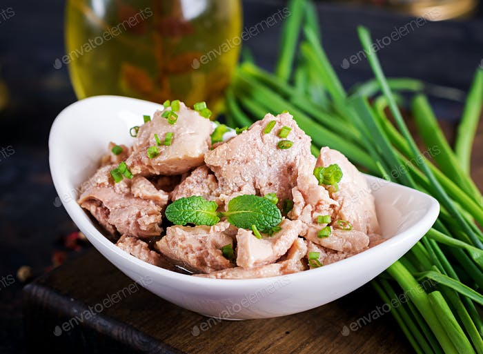 Cod liver with green onion in oil on plate.