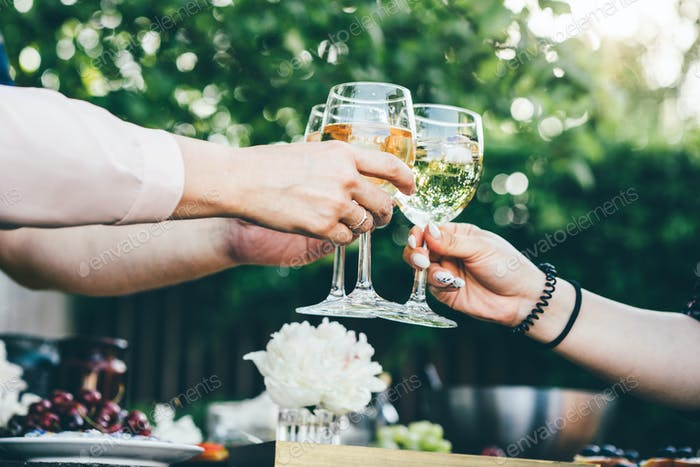 People holding glasses of white wine making a toast.