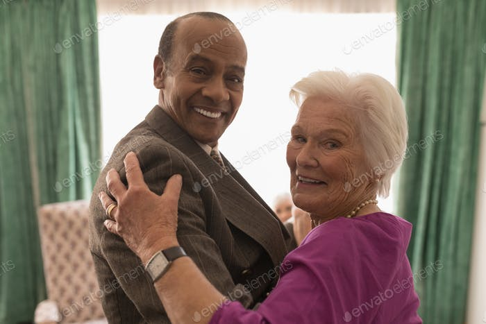 Side view of happy senior couple looking at camera while dancing and smiling at home
