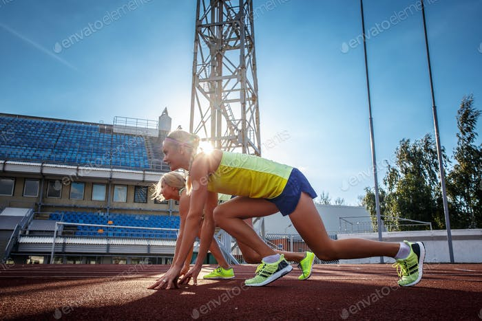 Two female sprinter athlete in the athletics stadium.