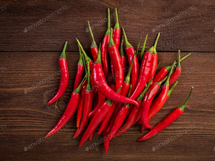 Red hot chili pepper on dark wooden background, top view.