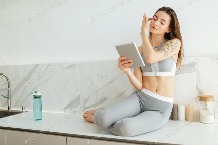 Young lady in sporty top and leggings sitting on kitchen with tablet thoughtfully looking aside