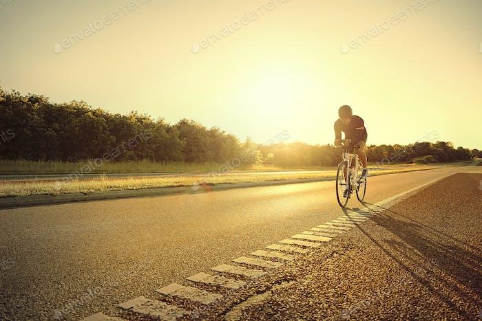 Person auf Rennrad allein auf der Autobahn