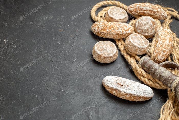 Verschiedene leckere Kekse auf Seil und alte Keramik auf schwarzem Hintergrund