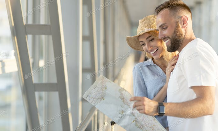 Travel together. Happy couple observing map, waiting for departure