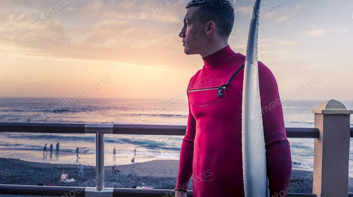 Young surf athlete look at the ocean waves standing with his surf table outdoor at the beach