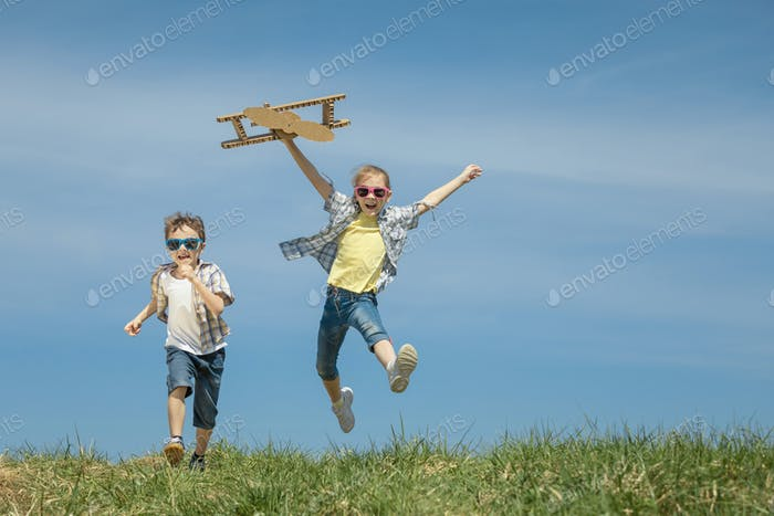 Little kids playing with cardboard toy airplane in the park at t