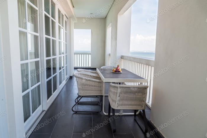 Relaxing balcony with table, chairs, fruits and with sea view