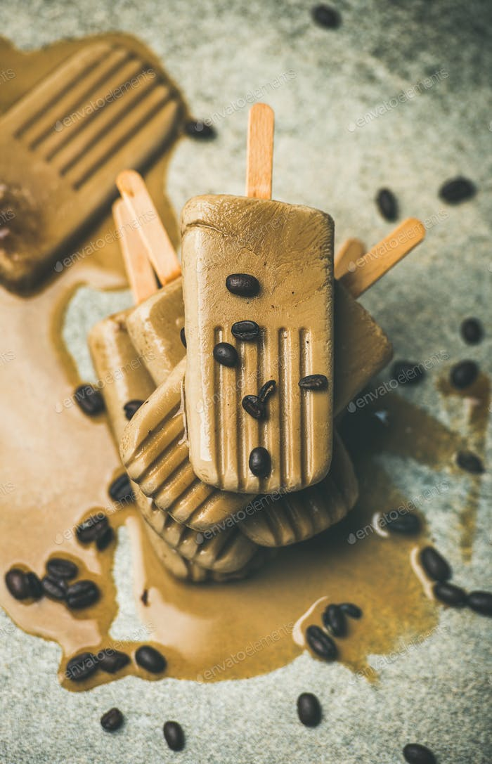 Melting coffee latte popsicles with roasted coffee beans, top view