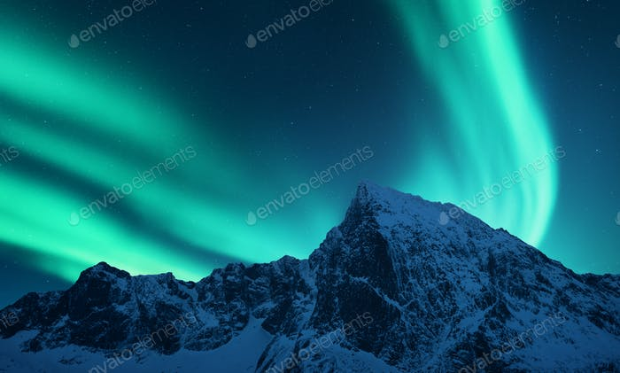 Aurora borealis above snow covered mountain range in europe