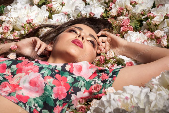 Gorgeous sensual woman lying on flowers