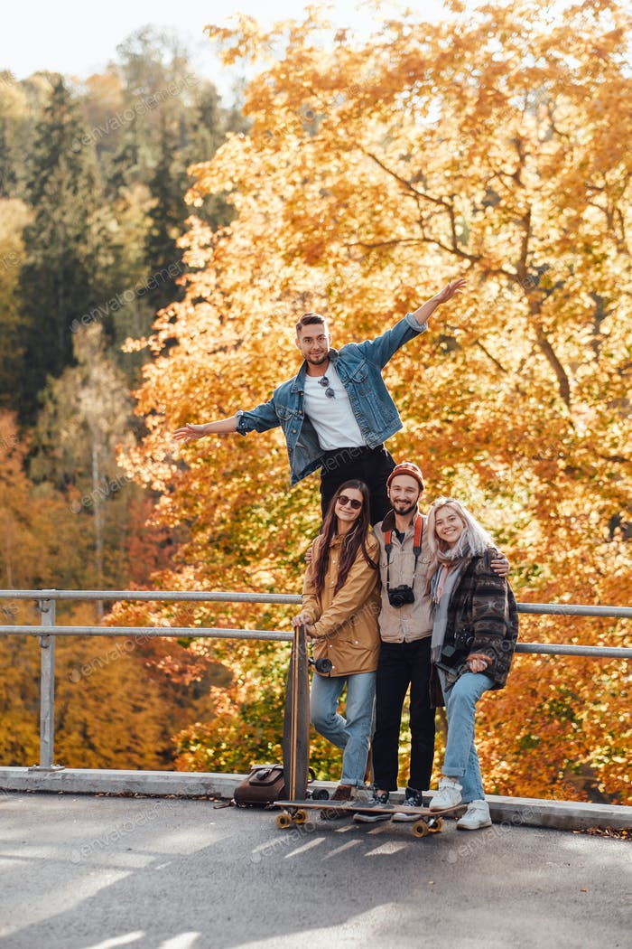 Carefree friends having a good time in autumn forest
