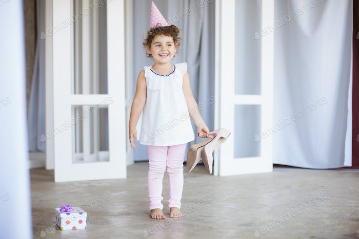 Cheerful little girl with dark curly hair in birthday cap happil