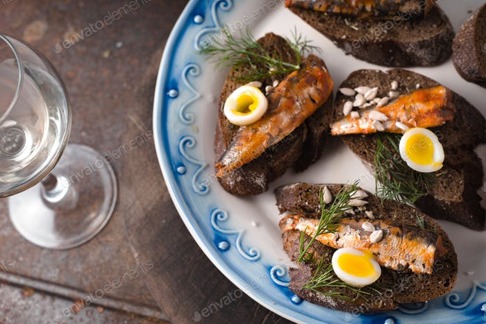 Sardines, quail egg on rye bread on a ceramic plate and glass