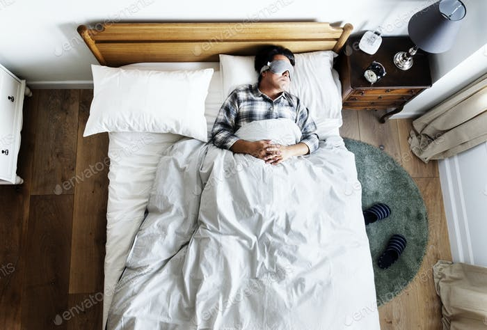 Japanese man sleeping on bed with eye mask