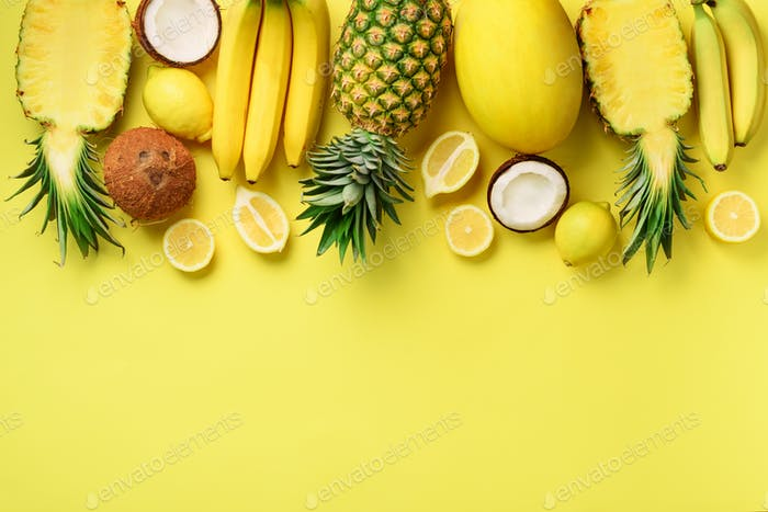 Fresh organic yellow fruits over sunny background. Monochrome concept with banana, coconut