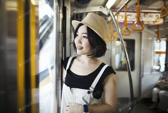 Young woman wearing a hat traveling on a train.