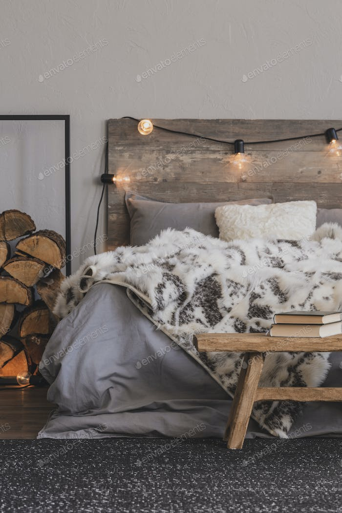 Wooden bench with book in foot of the bed of cozy bedroom interi