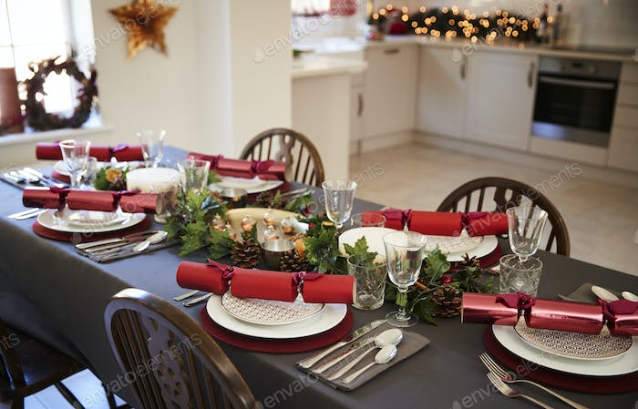 Christmas table setting with Christmas crackers arranged on plates