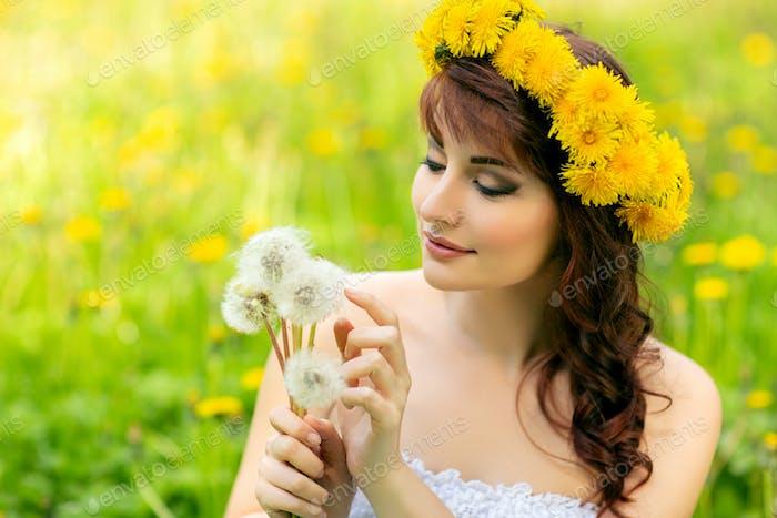 schönes Mädchen mit Löwenzahn Blumen in grünem Feld