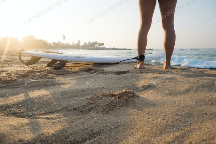 Young caucasian woman surfer with surfboard in the morning