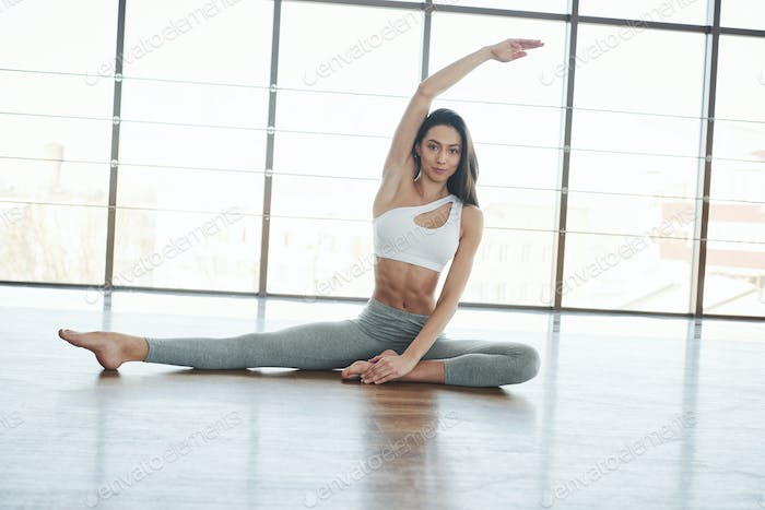 Another pose. European young brunette doing yoga in the room with big windows