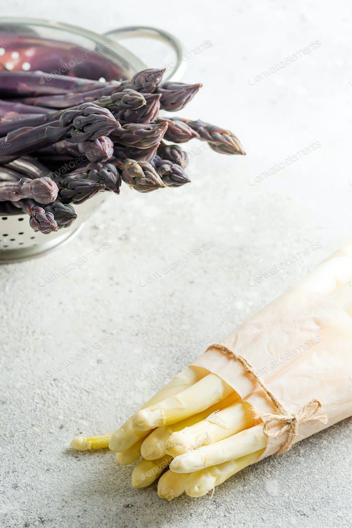 Rohes Bio-lila Spargelspeere im Sieb und Bündel von weißem Spargel als gesunde Ernährung