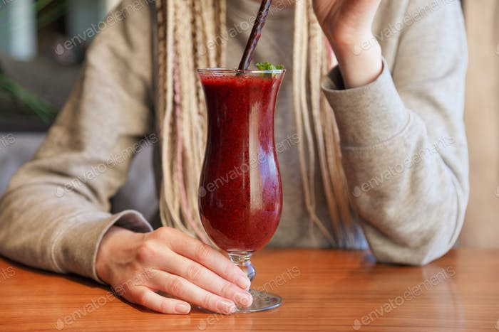 Glass of smoothie cocktail made of blackberry, blueberry, strawberry and vanilla in woman's hands