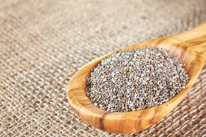 Close up picture of Chia seeds in a wooden spoon.
