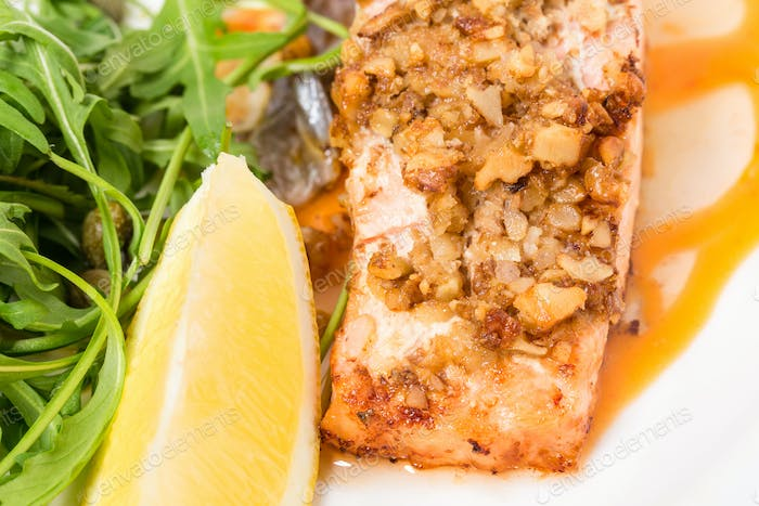 Baked salmon fillet with walnuts and arugula.