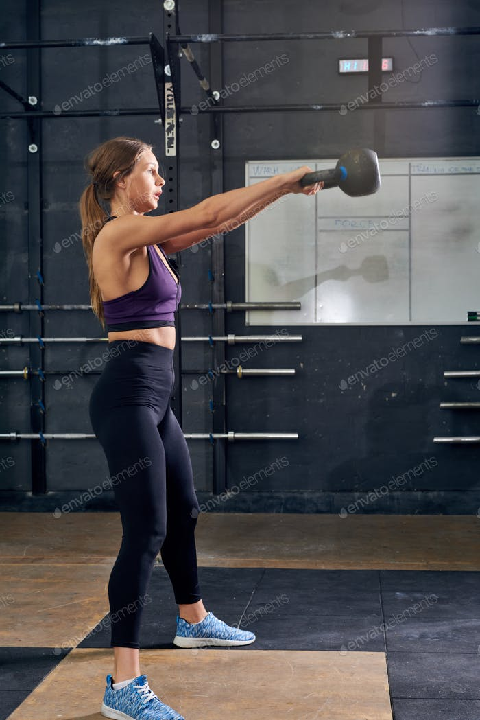 Young Woman Swinging Kettlebell in Modern Gym