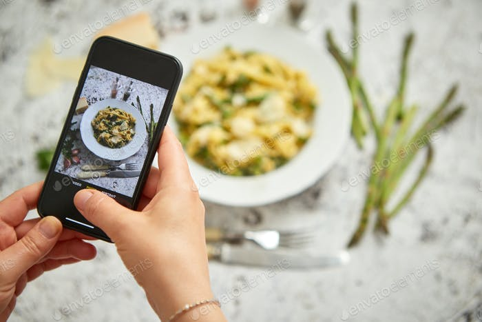 Frau macht ein Foto mit einem Smarpthone von hausgemachten Tagliatelle Pasta mit cremigem Ricotta