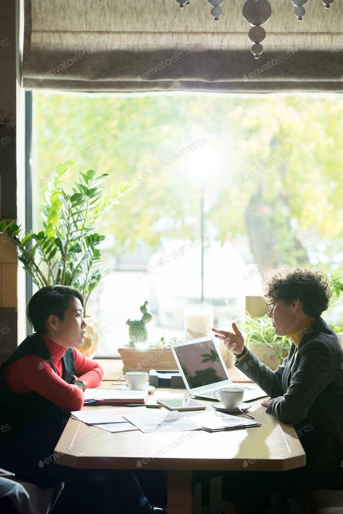 Confident business specialist explaining data to colleague