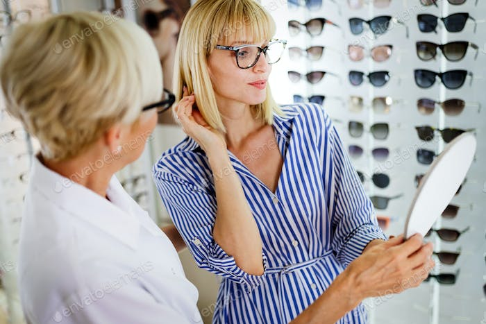 Health care, eyesight and vision concept. Happy woman choosing glasses at optics store