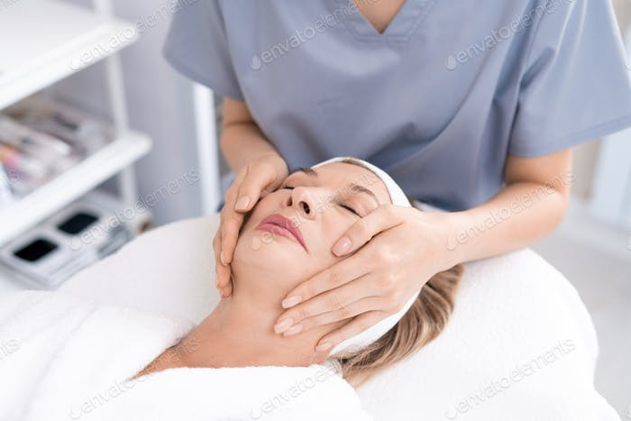 Giving facial massage in beauty salon