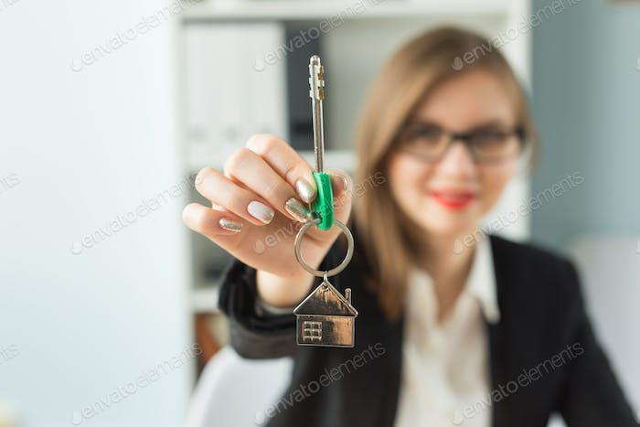 New home and real estate concept - Close up of happy realtor woman with red lips giving you keys